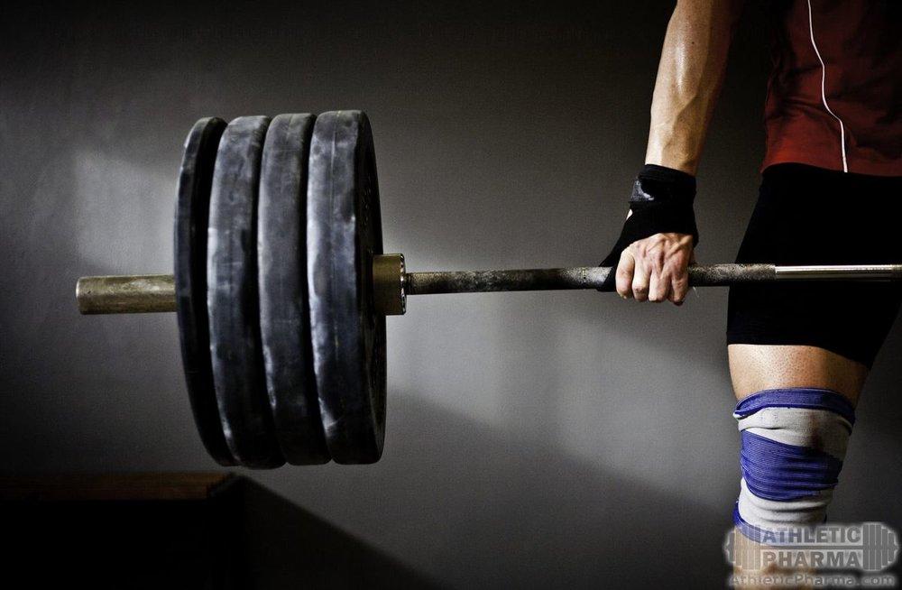 Спортсмен поднимает тяжелую штангу